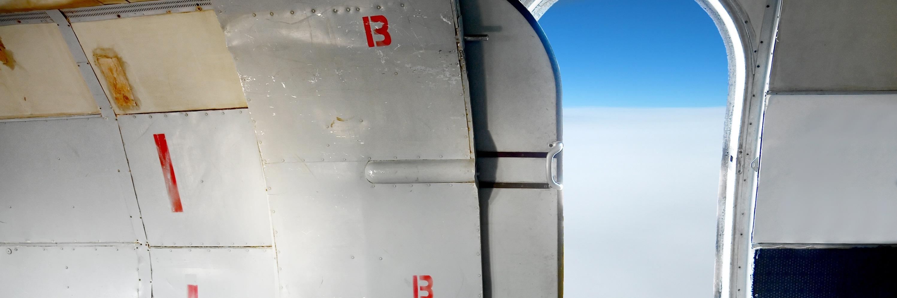 Plane interior with open cabin door high up in the sky